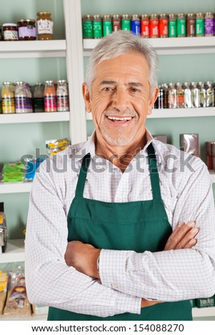 Portrait of senior male owner with hands folded smiling in grocery store - stock photo