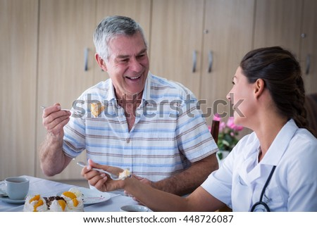 Portrait of senior man and female doctor having cake in living room at home