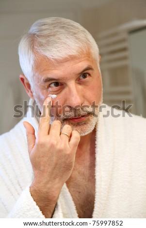 Portrait of senior man applying moisturizing cream - stock photo