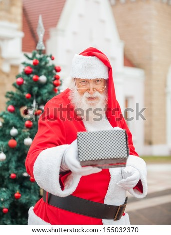Portrait of senior man dressed as Santa Claus giving gift against house - stock photo