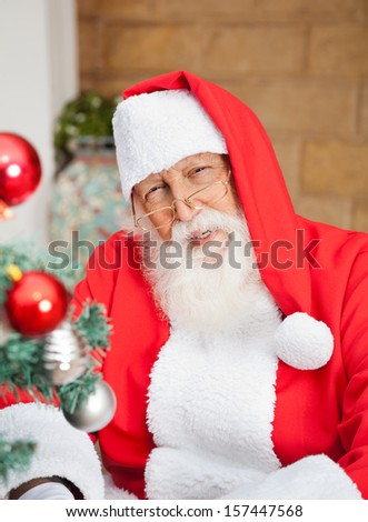 Portrait of senior man dressed as Santa Claus outside house - stock photo