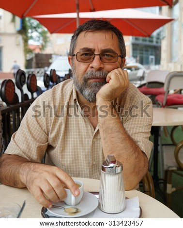 Portrait of senior man drinking cup of coffee while sitting outside