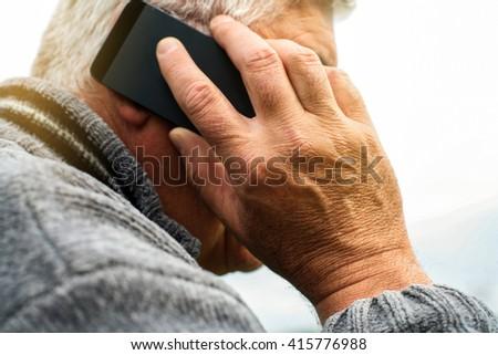 Portrait of senior man hands with smartphone. Focus on hands.  - stock photo