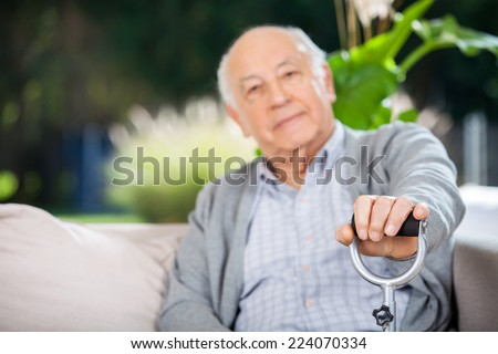 Portrait of senior man holding metal cane at nursing home porch - stock photo