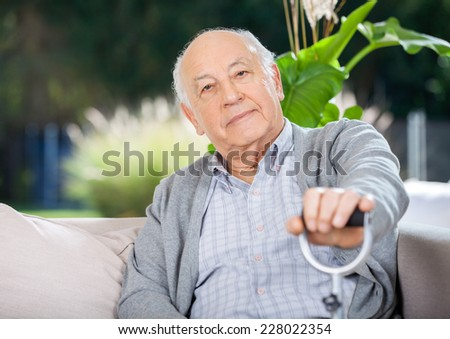 Portrait of senior man holding metal cane while sitting on couch in nursing home porch - stock photo