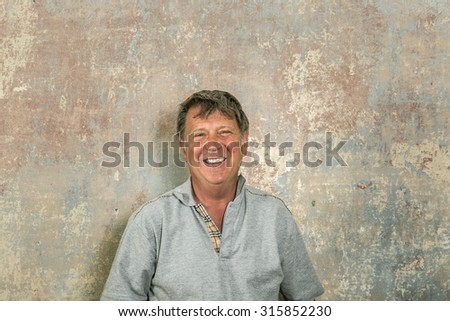 portrait of senior man in front of grungy old wall in a rotten house - stock photo