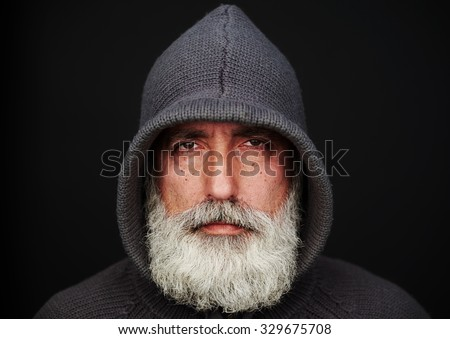 portrait of senior man in knitted jacket over black background. landscape orientation