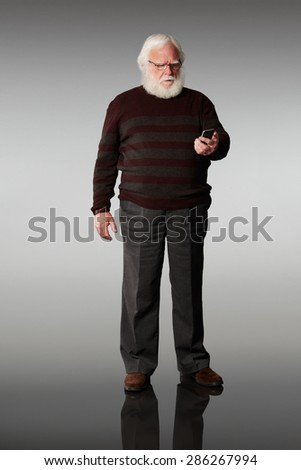 Portrait of senior man looking at his mobile phone seriously against grey background - stock photo