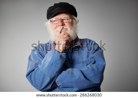 Portrait of senior man looking away and thinking with his hand on chin against grey background - stock photo