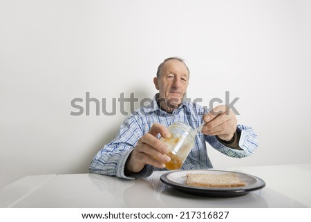 Portrait of senior man preparing slice of bread and marmalade at table