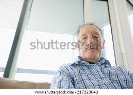 Portrait of senior man relaxing in living room - stock photo