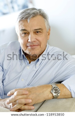 Portrait of senior man relaxing in sofa at home - stock photo