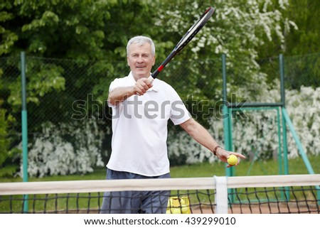 Portrait of senior man serving tennis ball while playing tennis match on court.