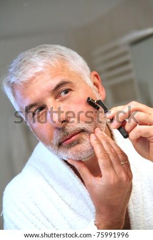 Portrait of senior man shaving beard - stock photo