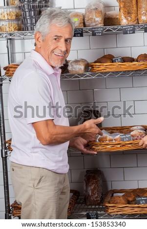 Portrait of senior man showing muffins in supermarket - stock photo