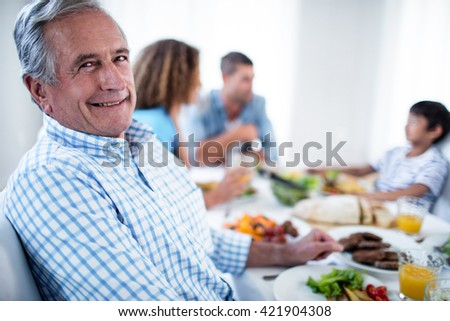 Portrait of senior man sitting at dinning table and family in background - stock photo