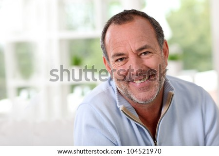 Portrait of senior man sitting in sofa at home