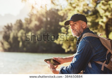 Portrait of senior man sitting near a lake with backpack and digital tablet. Mature male hiker sitting at a lake and looking away. - stock photo