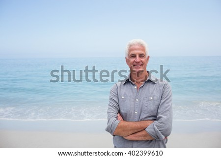 Portrait of senior man standing with arms crossed on beach on a sunny day - stock photo