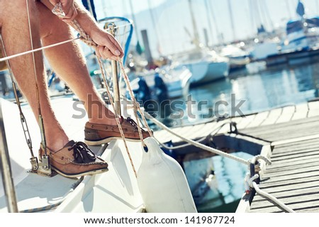portrait of senior man tying knot and securing a mooring for his hobby yacht sail boat - stock photo