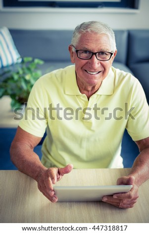 Portrait of senior man using digital tablet at home