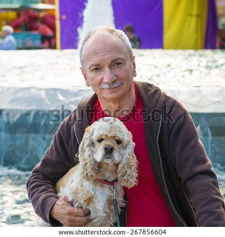 Portrait of senior man with a dog outdoors - stock photo