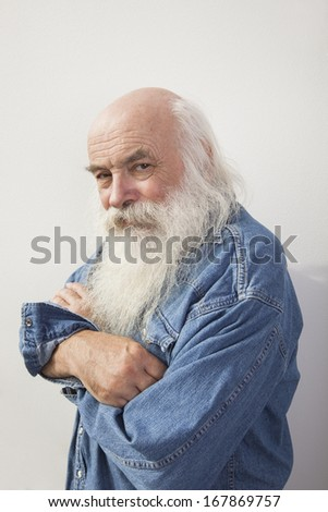 Portrait of senior man with arms crossed over gray background
