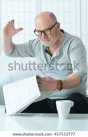 portrait of senior man with newspaper