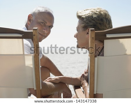 Portrait of senior man with woman sitting on deckchairs at beach - stock photo