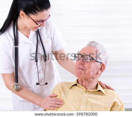 Portrait of senior man with young nurse holding her hand on his shoulder. Senior care concept - stock photo