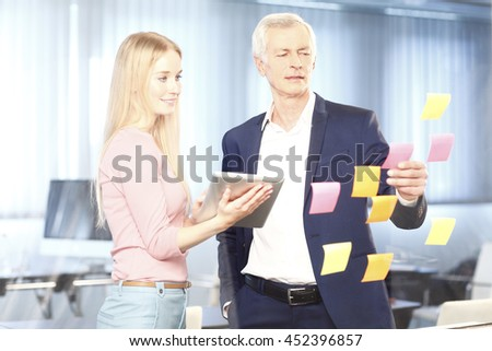 Portrait of senior manager and his young assistant working together while standing at idea board. Beautiful businesswoman holding using digital tablet while executive businessman reading sticky notes.