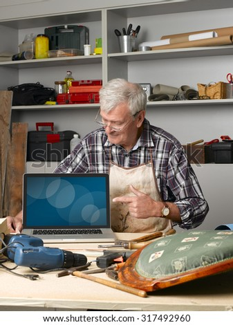 Portrait of senior manual worker sitting at his workshop in front of laptop and pointing his finger to the digitally generated image.