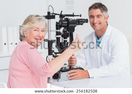 Portrait of senior patient gesturing thumbs up while sitting with optician in clinic - stock photo