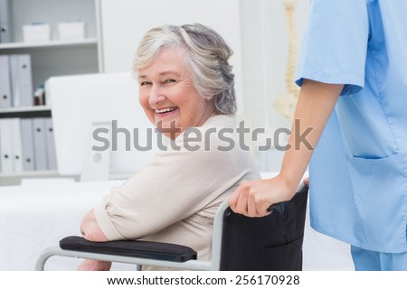 Portrait of senior patient in wheelchair being pushed by nurse at clinic - stock photo