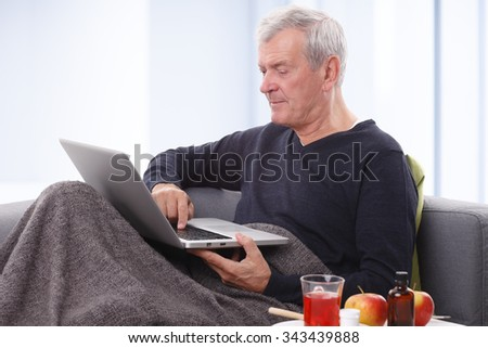 Portrait of senior patient man relaxing at home while using laptop and reading news.