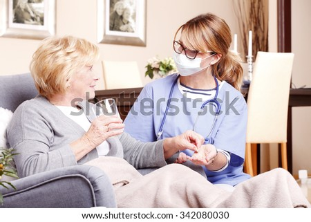 Portrait of senior patient sitting at home with home care nurse and giving medication to an elderly woman.