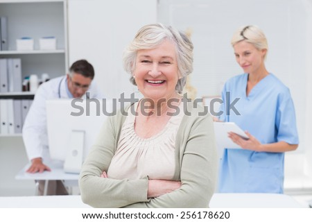 Portrait of senior patient smiling while doctor and nurse working in background at clinic - stock photo
