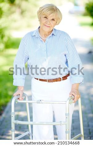 Portrait of senior patient walking outside - stock photo