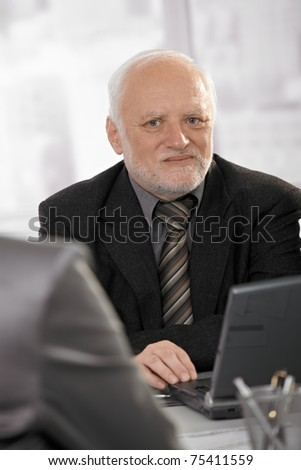 Portrait of senior professional looking at camera, using laptop computer at meeting.?