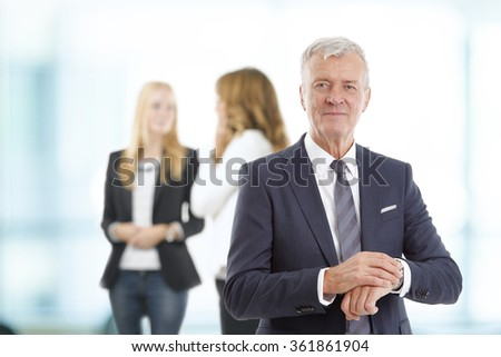 Portrait of senior professional man checking the time on his wristwatch while standing at office after meeting while business people standing at background.