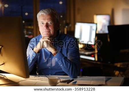 Portrait of senior professional man thinking about how to solve the problem while sitting at office in front of computer and working late.  - stock photo
