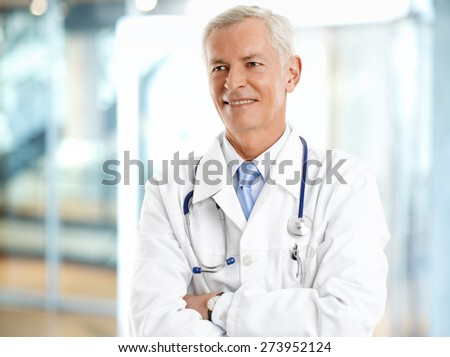 Portrait of senior professor standing at hospital with arms crossed and smiling. - stock photo