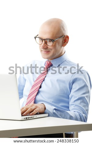 Portrait of senior sales man working with laptop while sitting at white background.  - stock photo