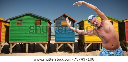Portrait of senior swimmer exercising against colorful huts on sand at beach