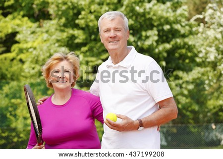 Portrait of senior tennis trainer playing tennis with active elderly woman.