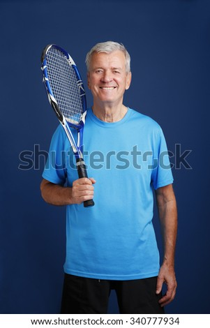 Portrait of senior tennis trainer standing against isolated background while holding in his hand a tennis racket.  - stock photo