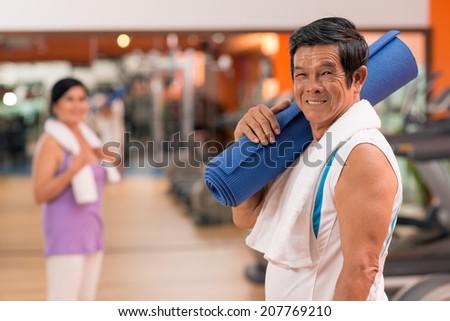 Portrait of senior Vietnamese man with yoga mat - stock photo