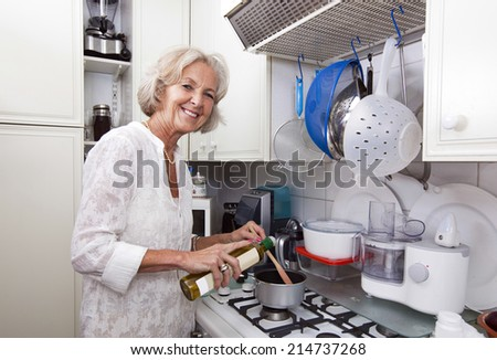 Portrait of senior woman adding olive oil to saucepan at kitchen counter - stock photo