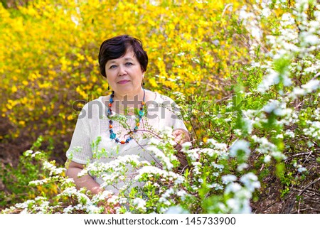 Portrait of senior woman against spring blossom - stock photo