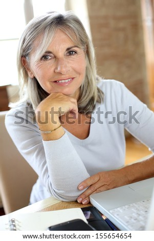 Portrait of senior woman at home using laptop